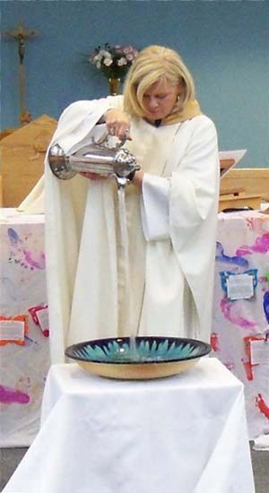 Reverend June Hough pours water for a baptism