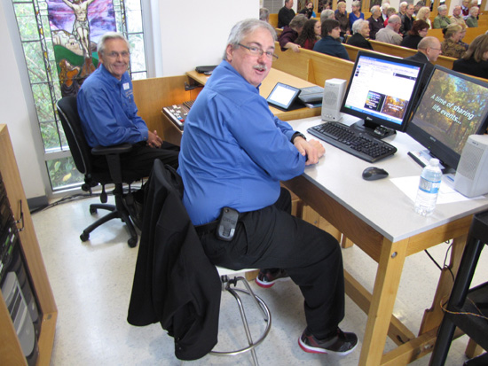 Bob and Philip, two members of the Audio-Video Team, operate the sound and PowerPoint systems during a church service.