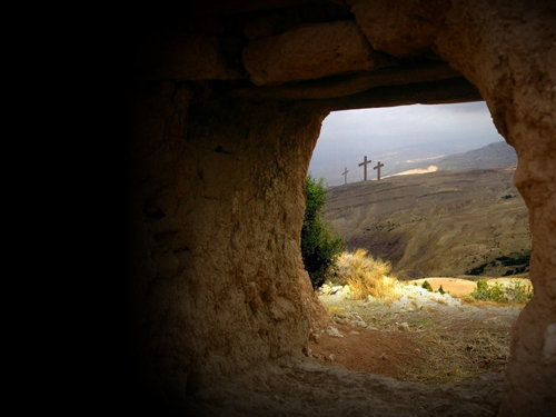 Looking out from empty tomb to empty crosses