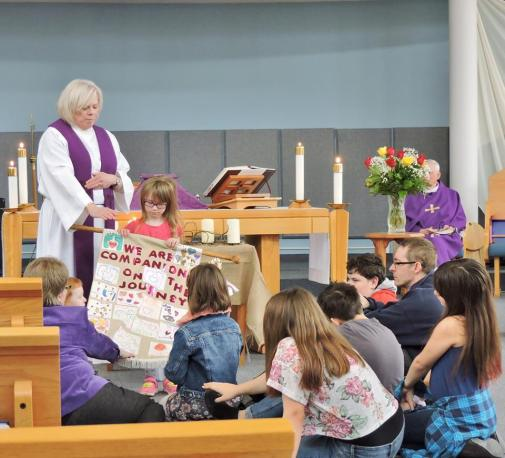 Children present a banner to Reverend June Hough